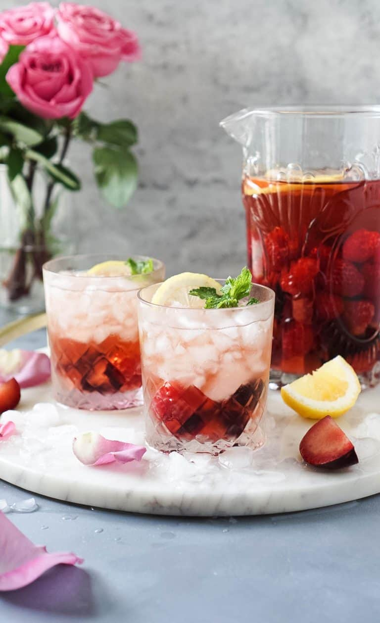 rose' sangria in two glasses and a pitcher with a vase of roses