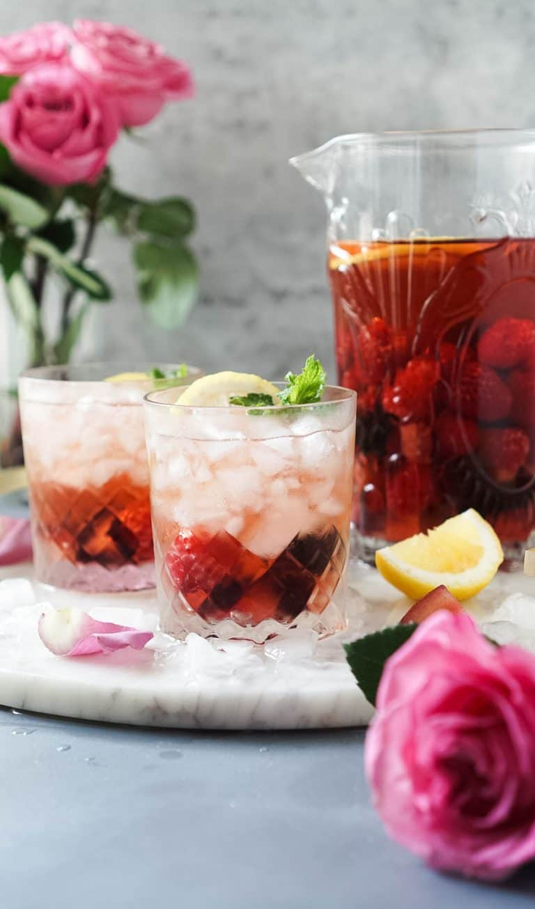 rose' sangria in a pitcher and two glasses with a rose and lemon wedge