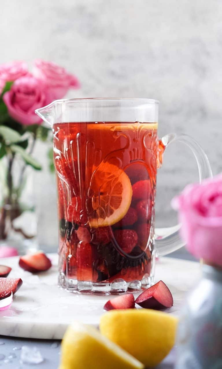 rose' sangria in a pitcher with fruit on the sides and roses
