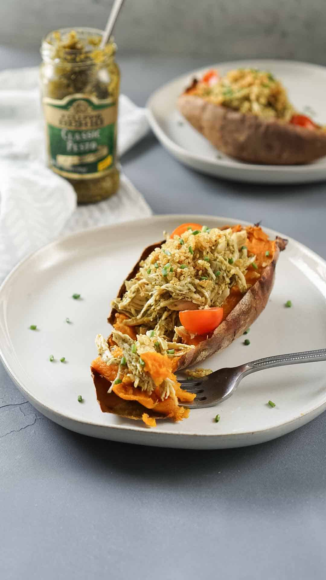 stuffed sweet potato on a white plate with a fork