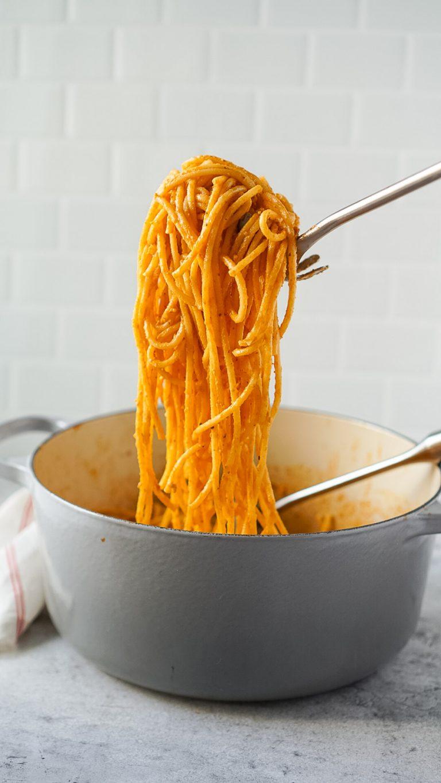 a pasta ladle lifting pesto pasta out of a grey le cruset pot