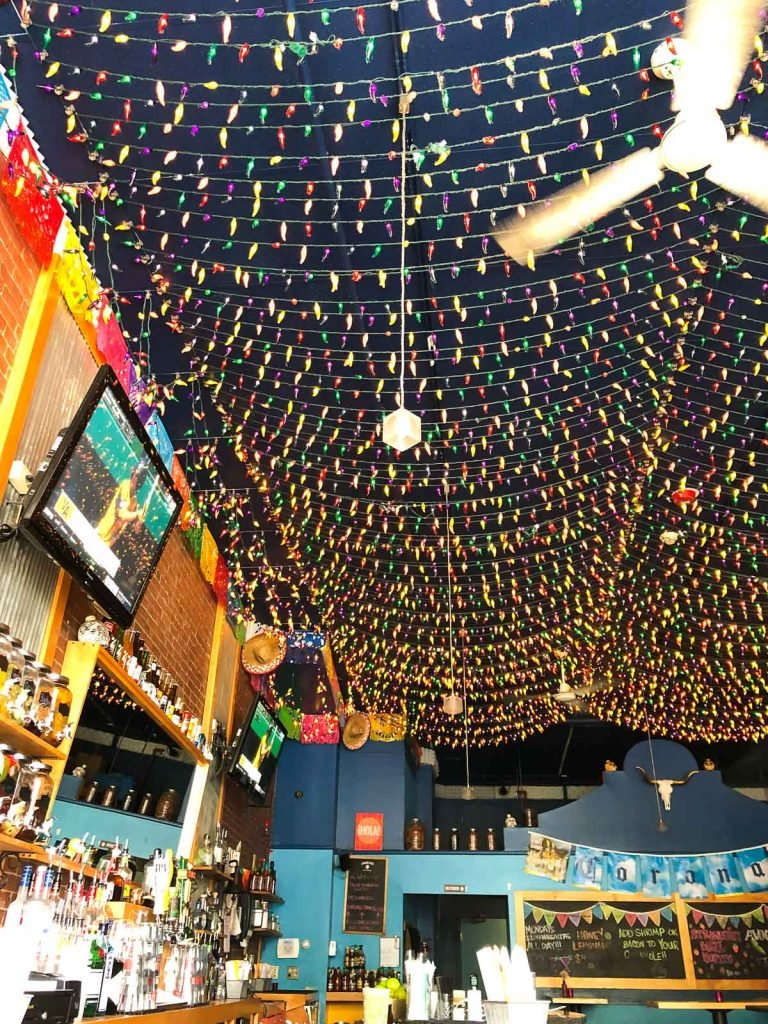 a restaurant with colorful string lights hanging from the ceiling
