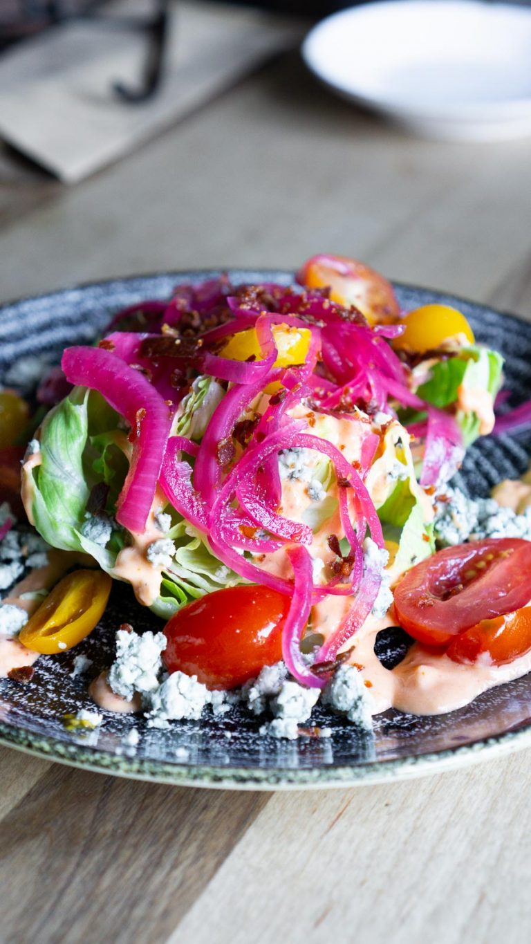 wedge salad with pickled onions, tomatoes, and blue cheese