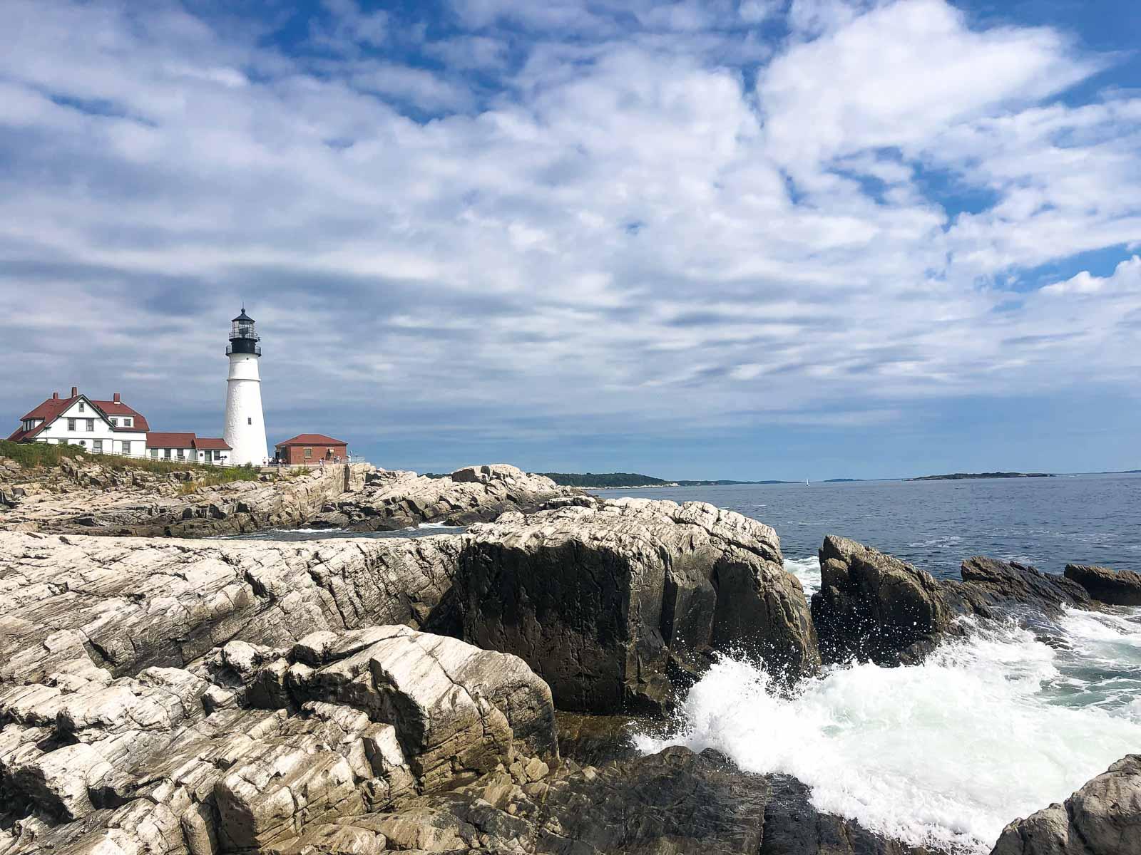 landscape photo of the portland head lighthouse with waves crashing on rocks