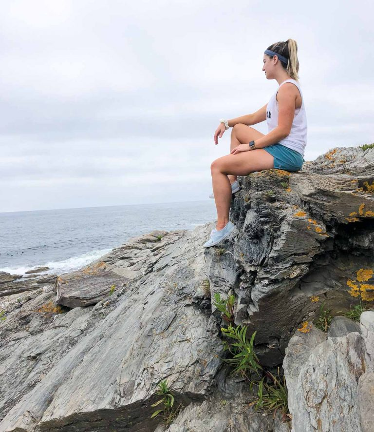 a girl with blonde hair sitting on the edge of a rock in shorts and a white shirt