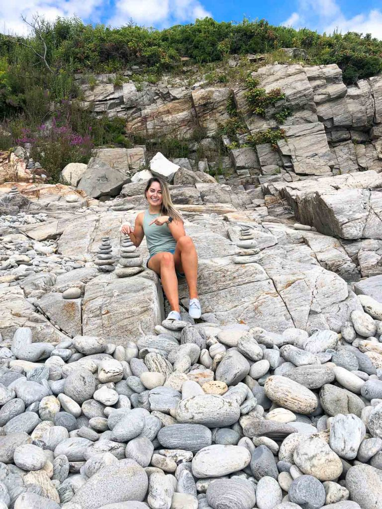 a girl sitting on rocks at fort williams park