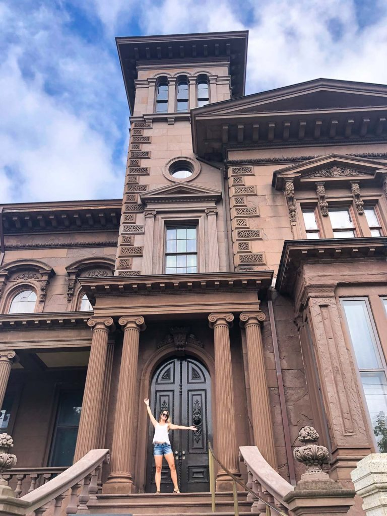 a girl standing outside the victoria mansion in portland maine