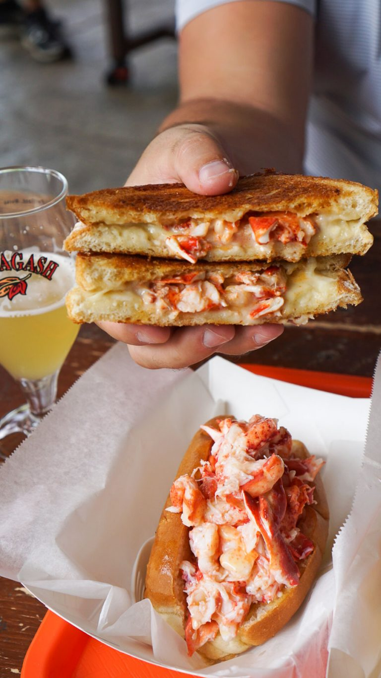 a hand holding a lobster grilled cheese with a beer and a lobster roll