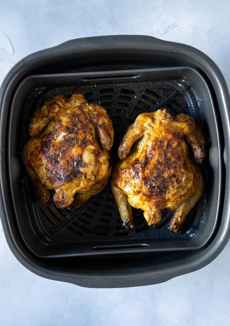 two cooked cornish hens in the air fryer basket