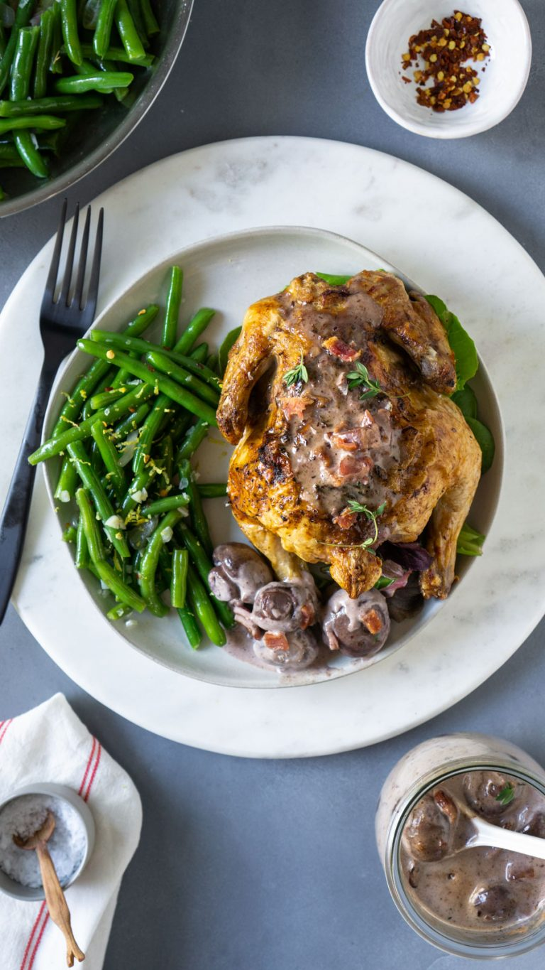 green beans, a cornish hen, and mushroom gravy on a white plate with a black fork
