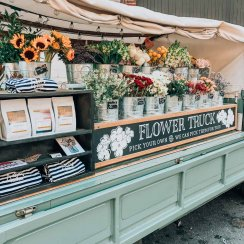 a flower stand on a light blue truck