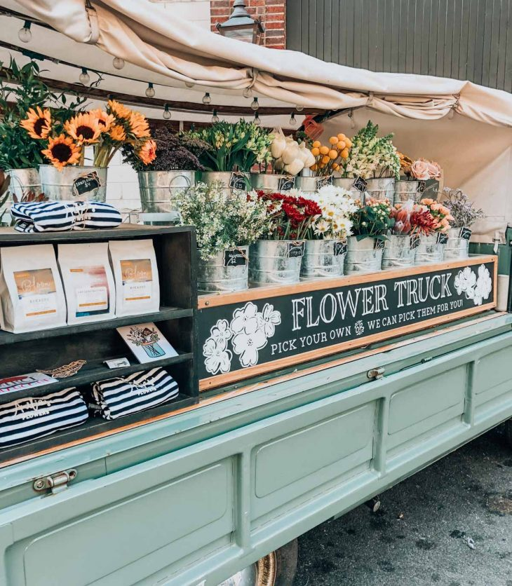 a flower stand on a light blue truck