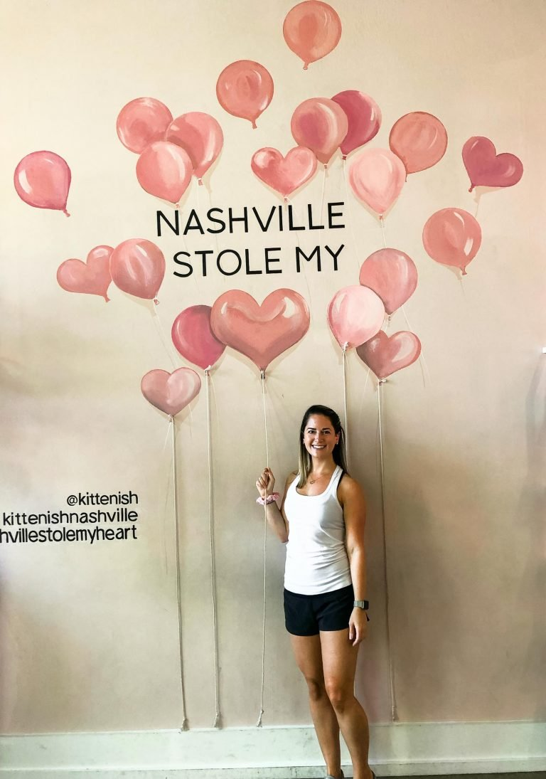 a girl standing in front of a mural with heart balloons