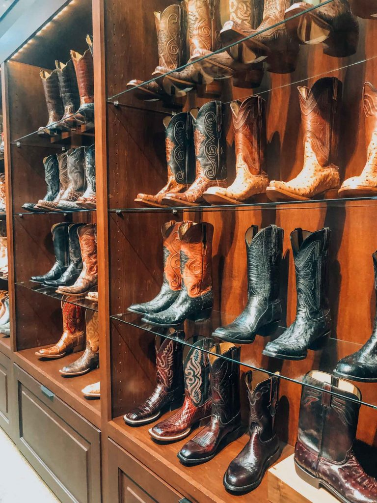 a wall lined with cowboy boots