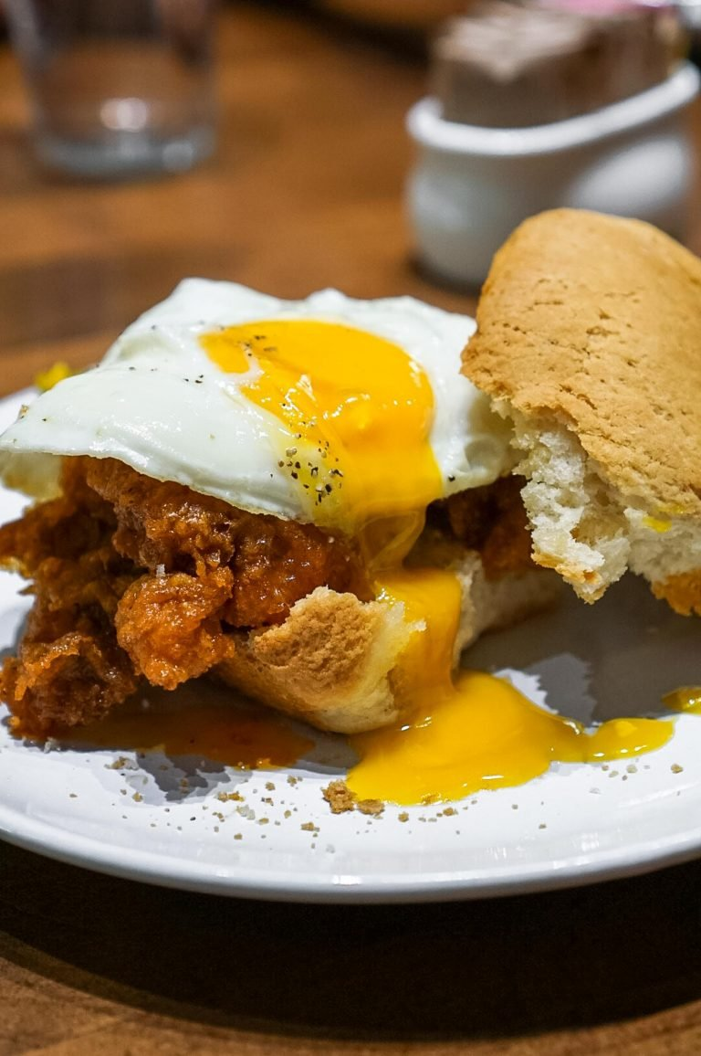 fried chicken sandwich with an egg and yolk dripping