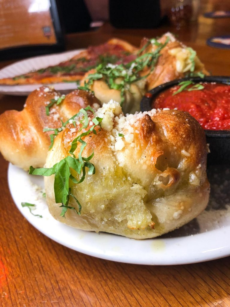 garlic knots on a white plate with marinara sauce