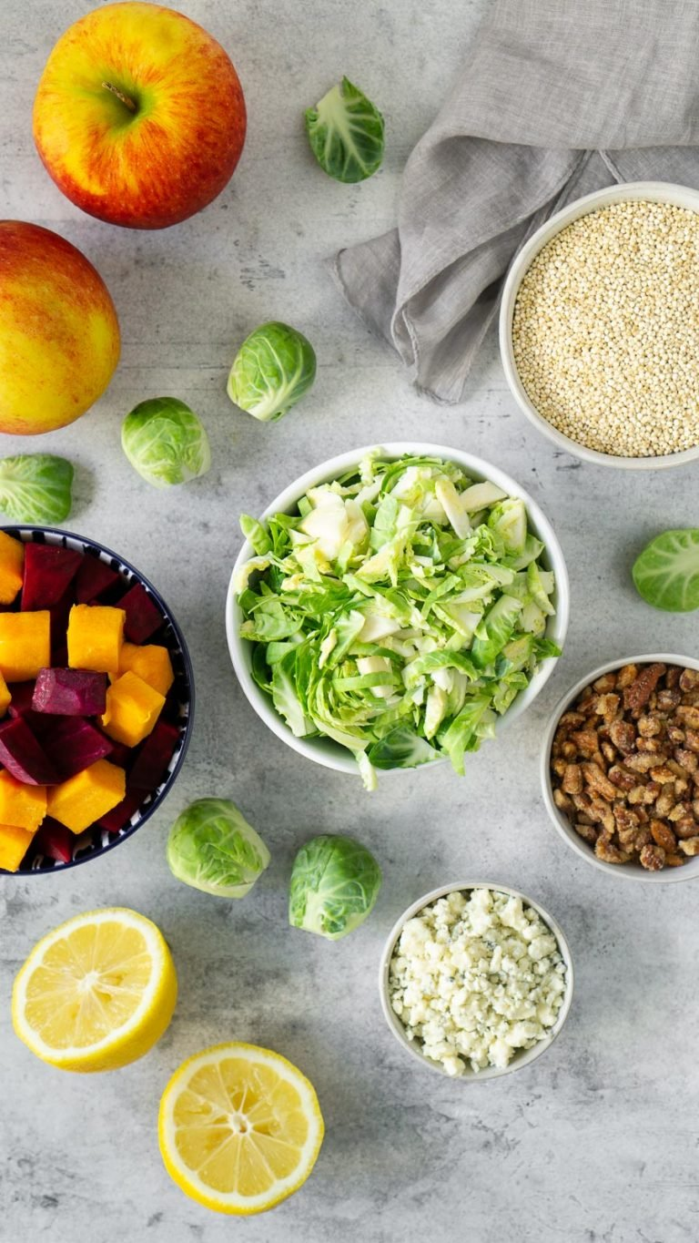 shredded brussels sprouts, beets, candied nuts, and quinoa in small bowls