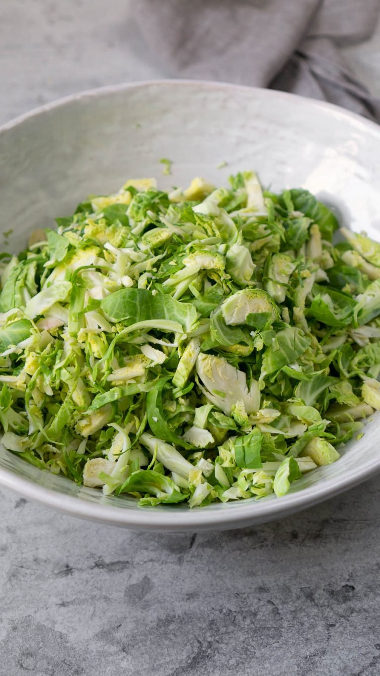 shredded brussels sprouts in a large white bowl