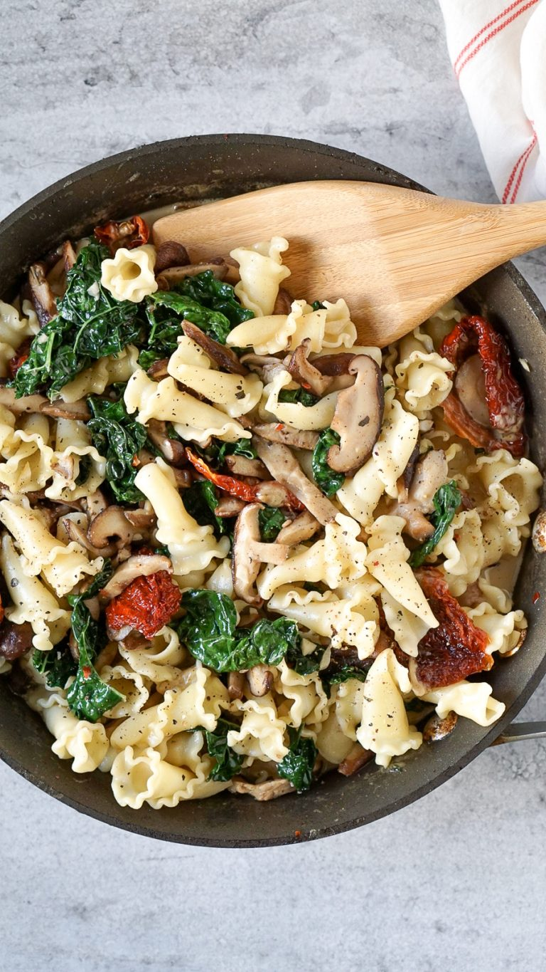 kale, sun dried tomatoes, and pasta in a pan with a wooden spatula