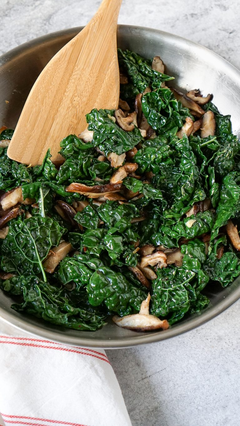 kale and mushrooms in a pan with a wooden spatula
