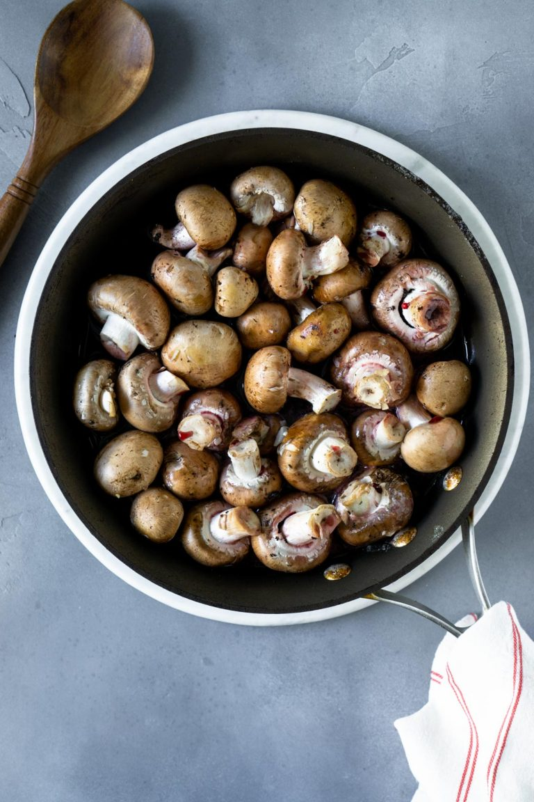 mushrooms in a skillet with a wooden spoon