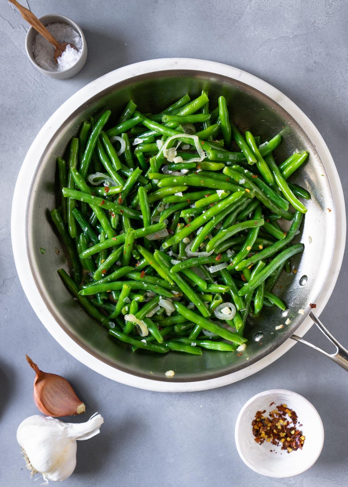 overhead shot of sautéed green beans, shallot, and garlic