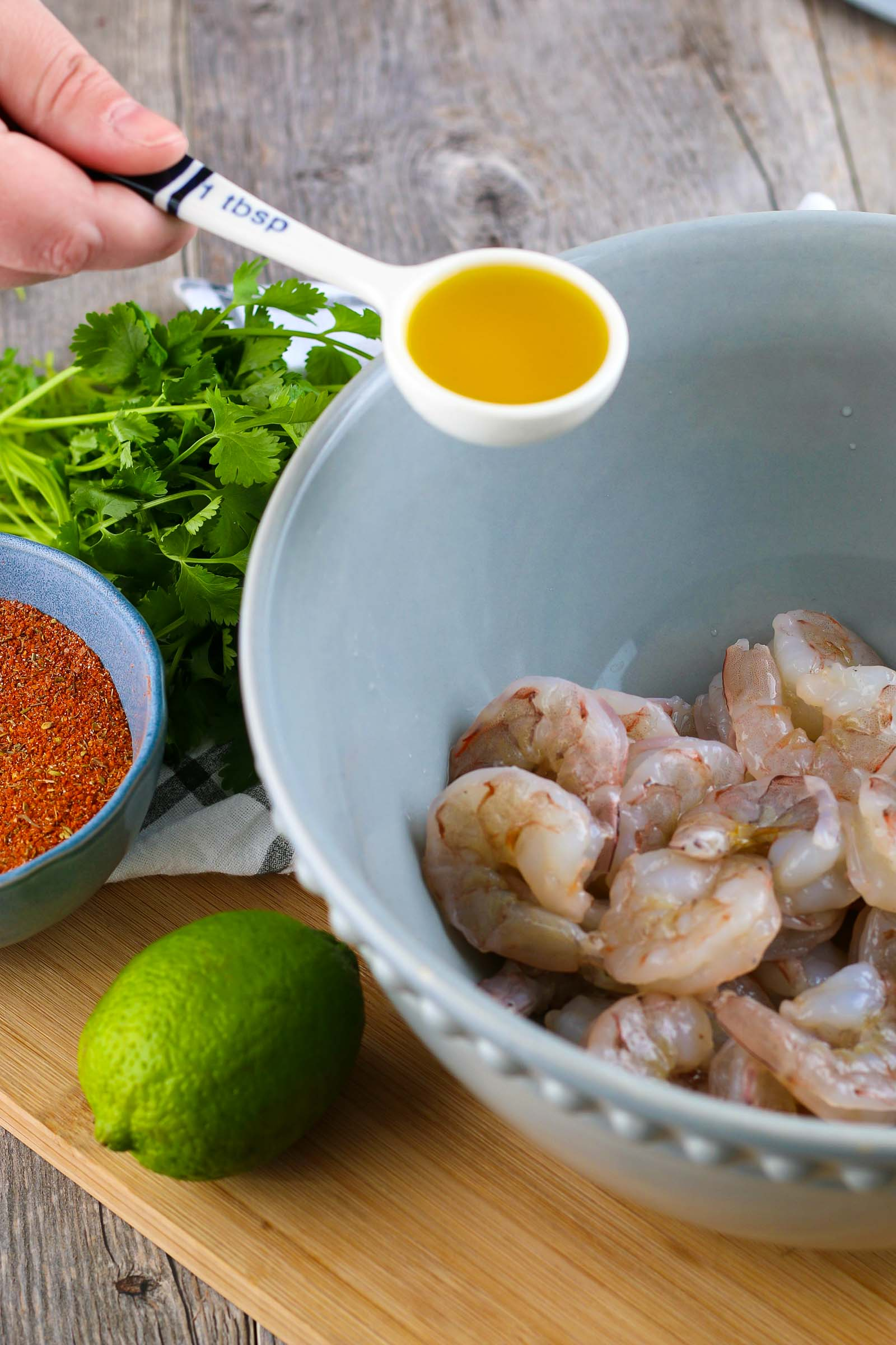 raw shrimp in a blue bowl and a tablespoon of olive oil