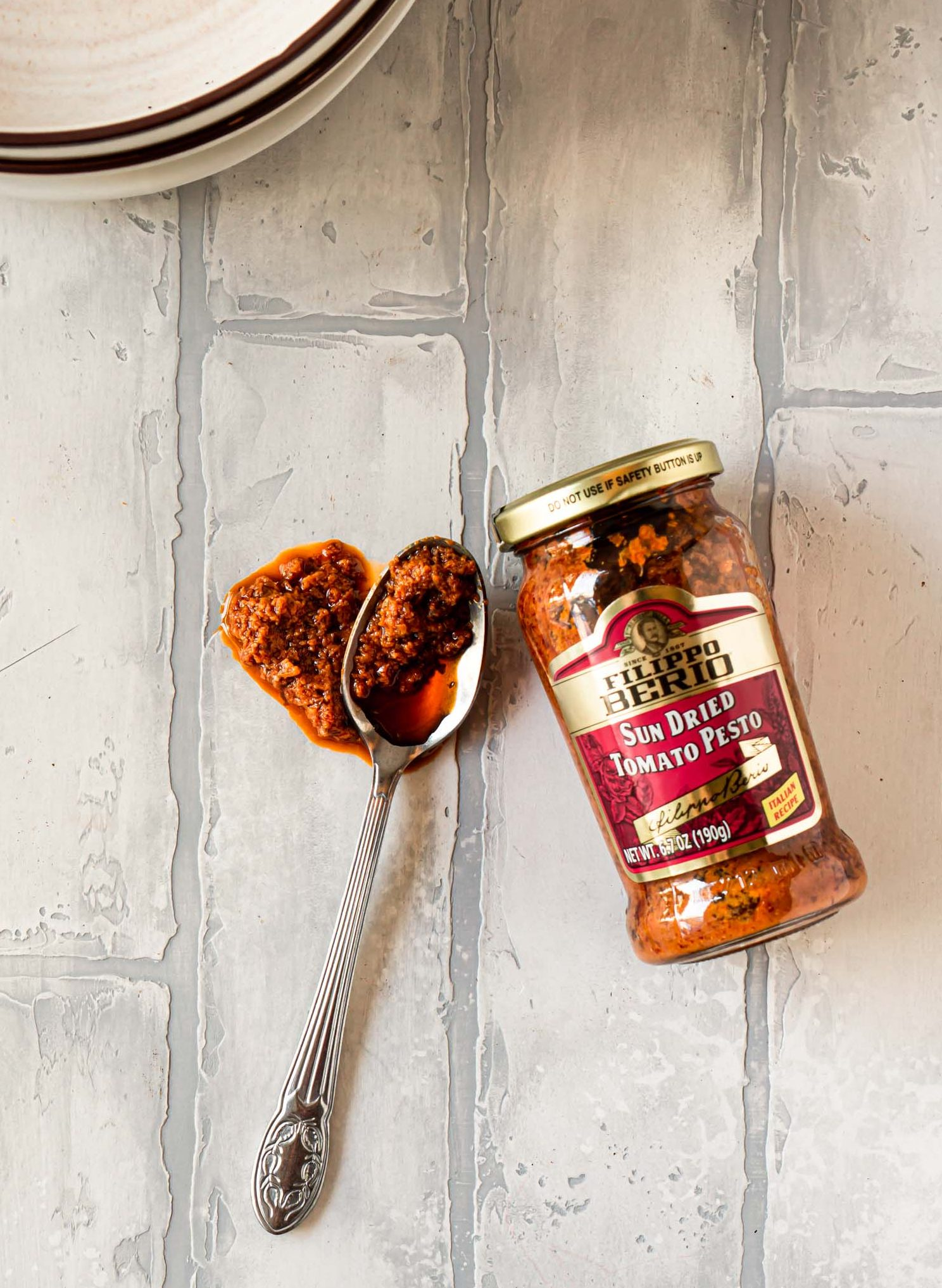 a jar of filippo berio sun dried tomato pesto and a silver spoon with pesto