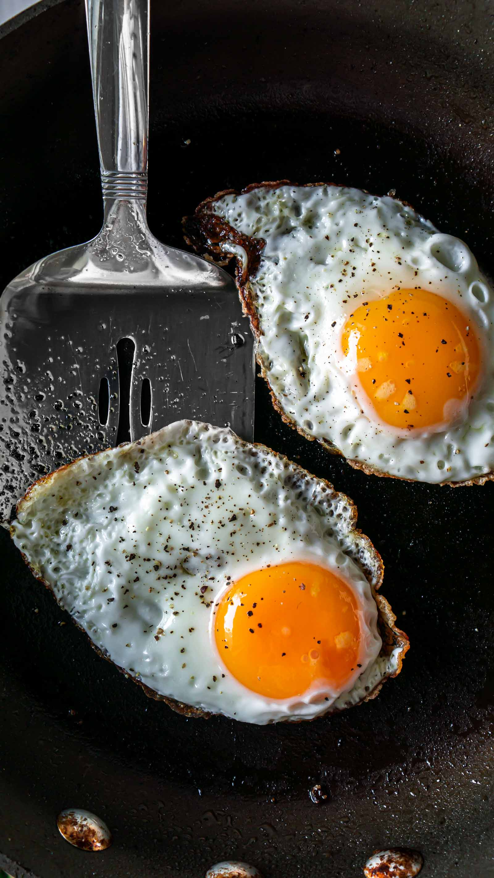 two fried eggs in a pan with a spatula