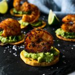 guacamole shrimp bites on a black board