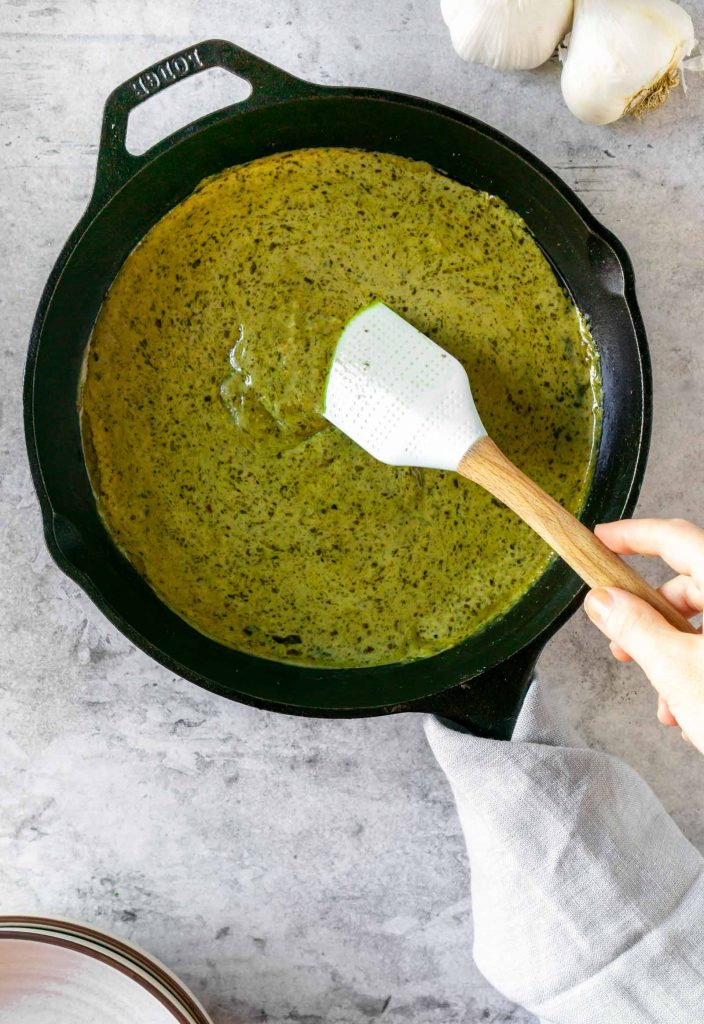 a spatula mixing the creamy basil pesto sauce
