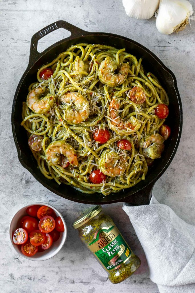 basil pesto shrimp pasta in a cast iron pan with a bowl of tomatoes, garlic, and a jar of pesto