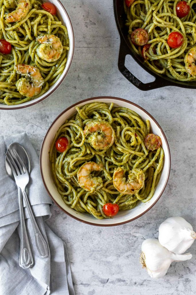 two bowls of basil pesto shrimp pasta, a spoon and a fork