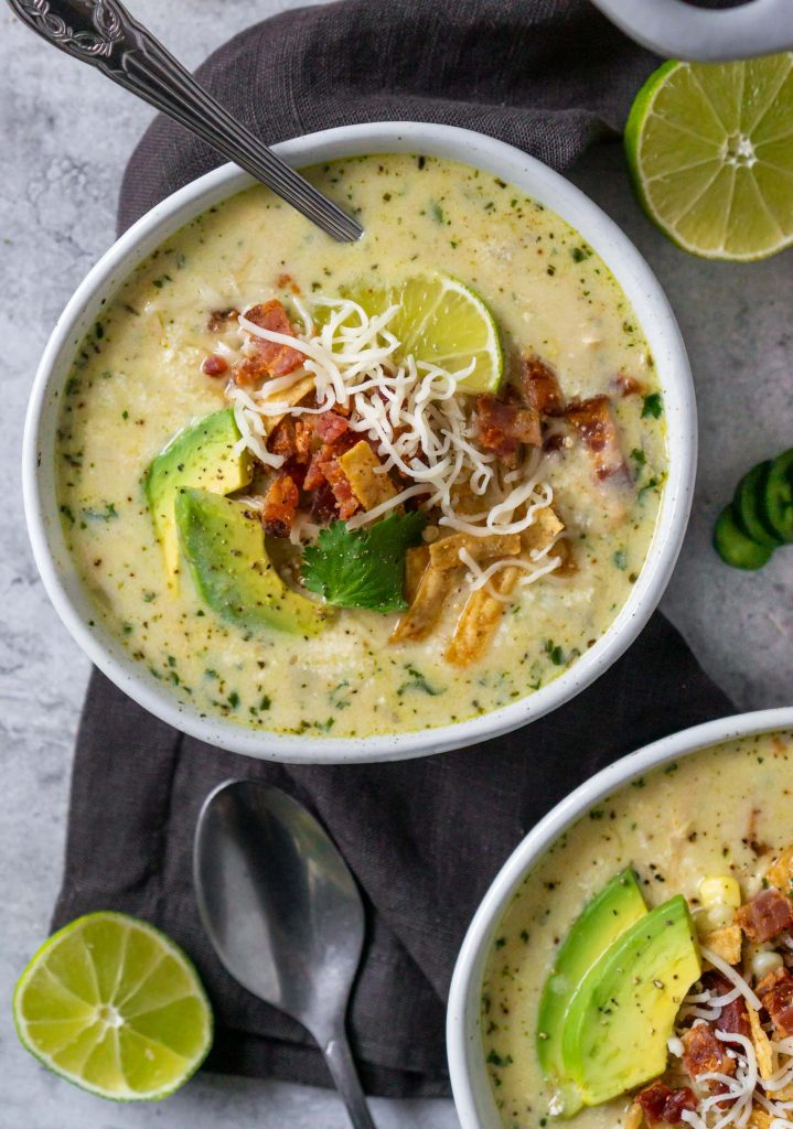 white chicken chili in a bowl with a silver spoon and two limes sliced in half