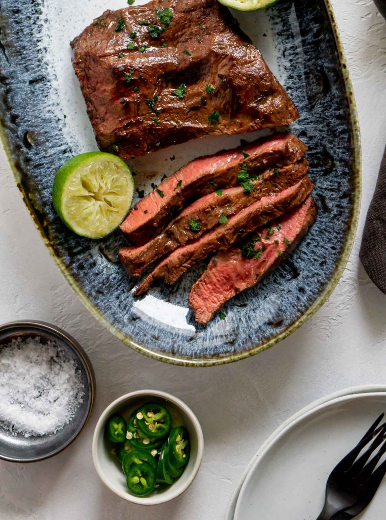 flank steak sliced on a blue plate