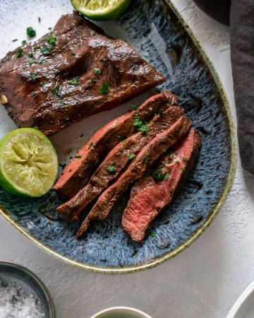 air fryer steak sliced on a blue plate with limes