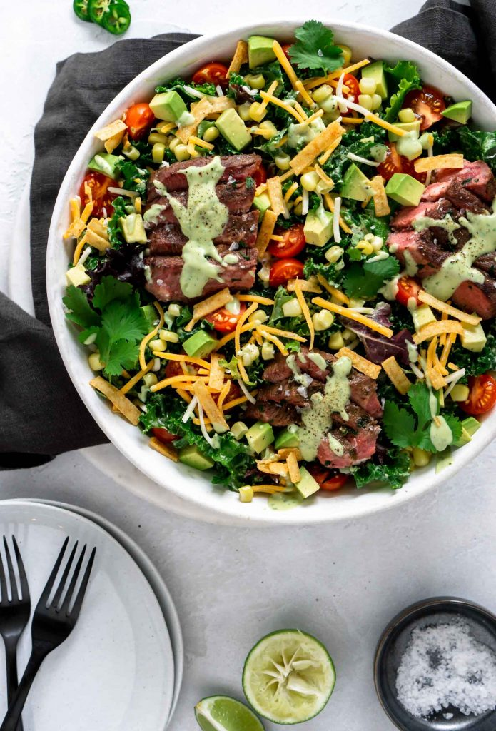 flank steak salad in a large white bowl