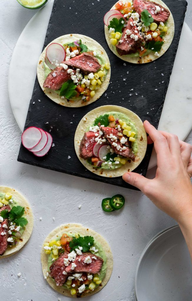 flank steak tacos on a black serving board and a hand reaching for one