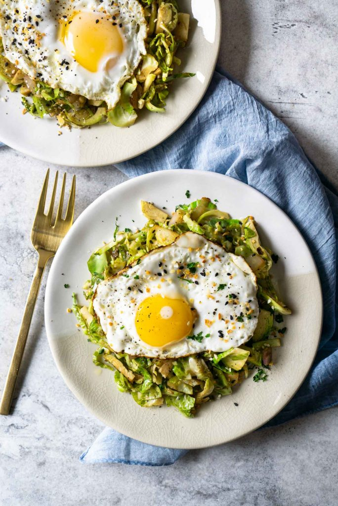 brussels sprouts hash with a fried egg on a plate and a blue napkin