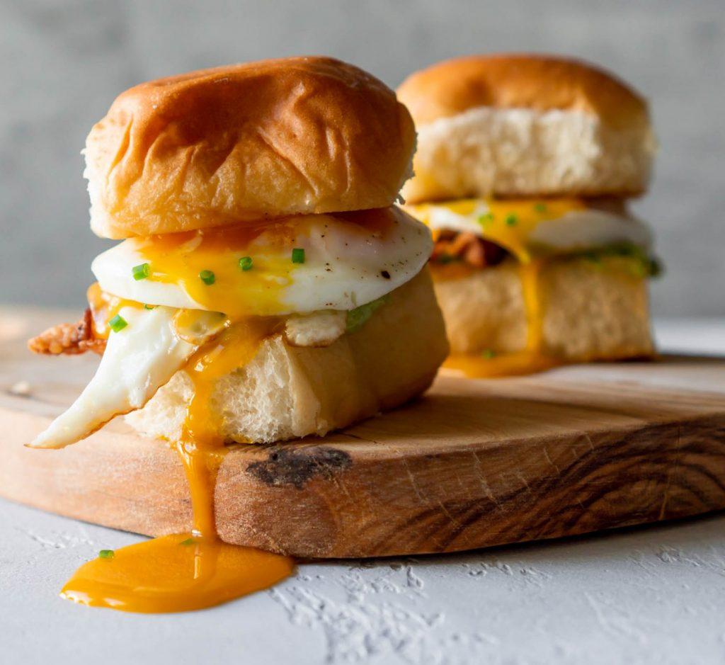 two breakfast sandwich sliders on a wood board