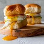 two breakfast sandwich sliders on a wood board