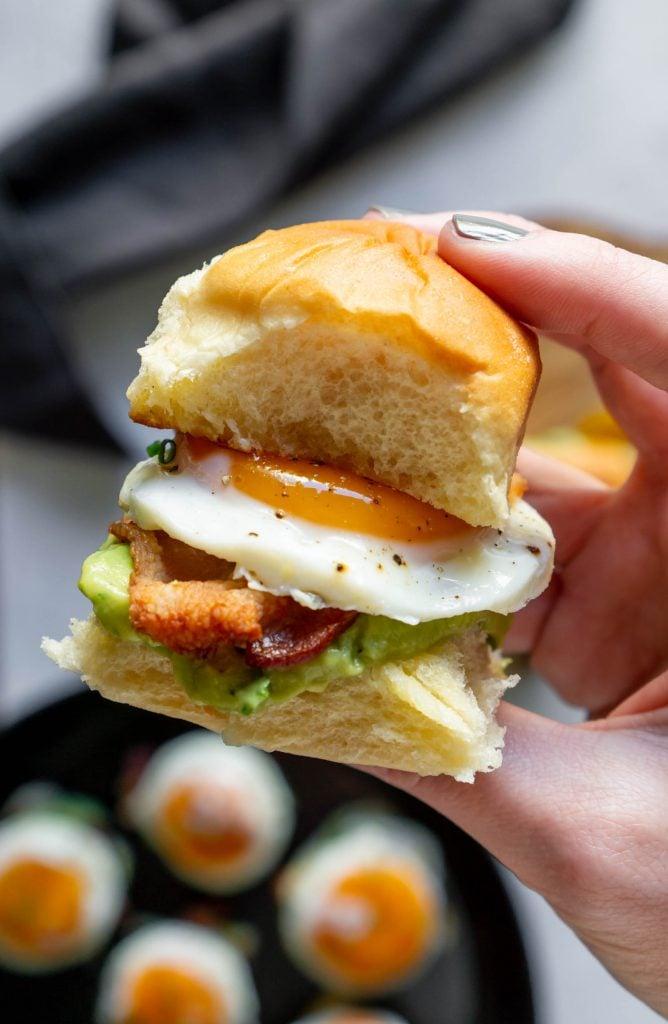 a hand holding a mini breakfast sandwich