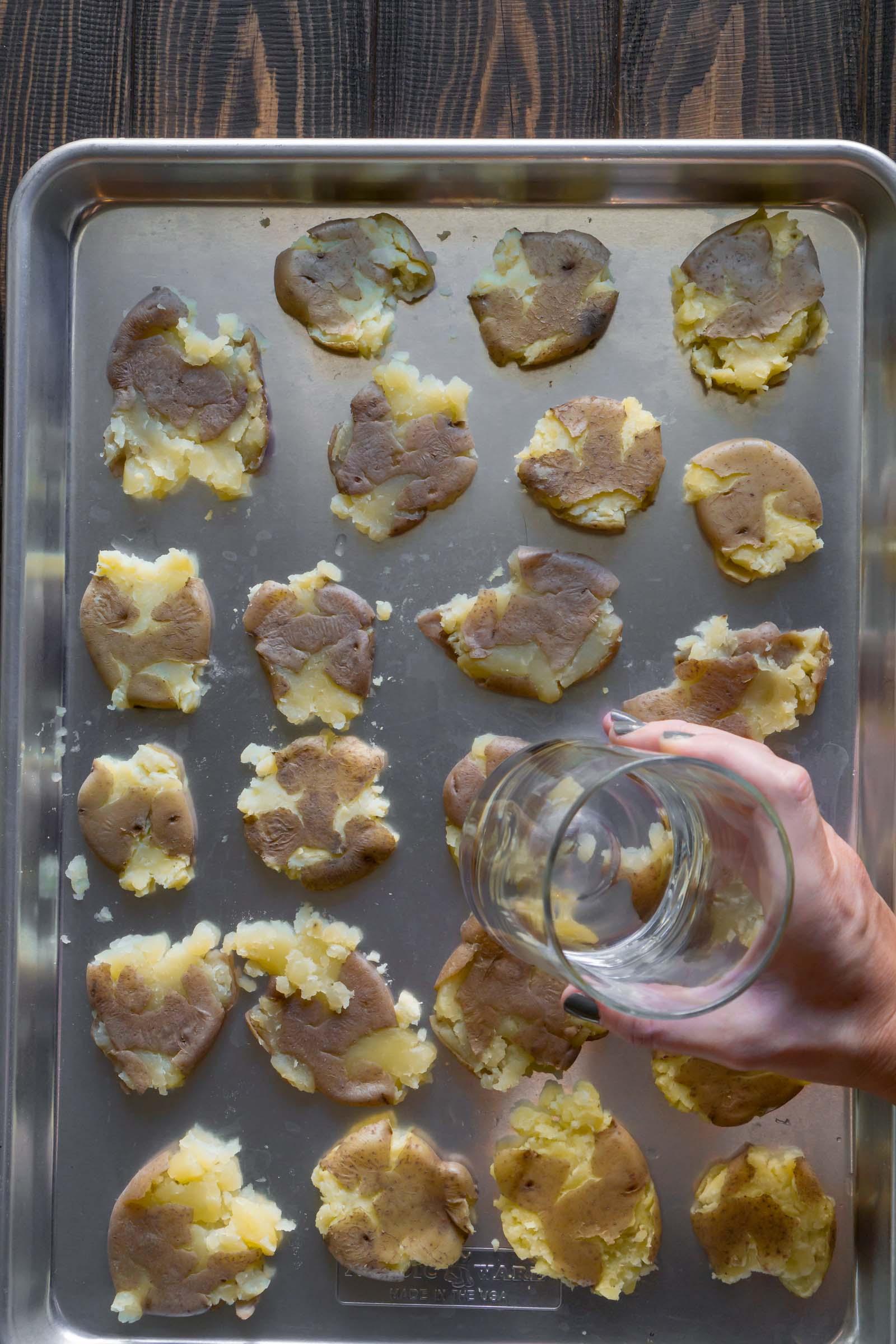 a glass smashing potatoes on a baking sheet