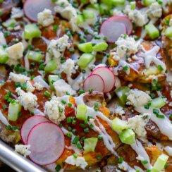 close up photo of crispy smashed potatoes loaded nachos