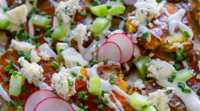 close up photo of crispy smashed potatoes loaded nachos