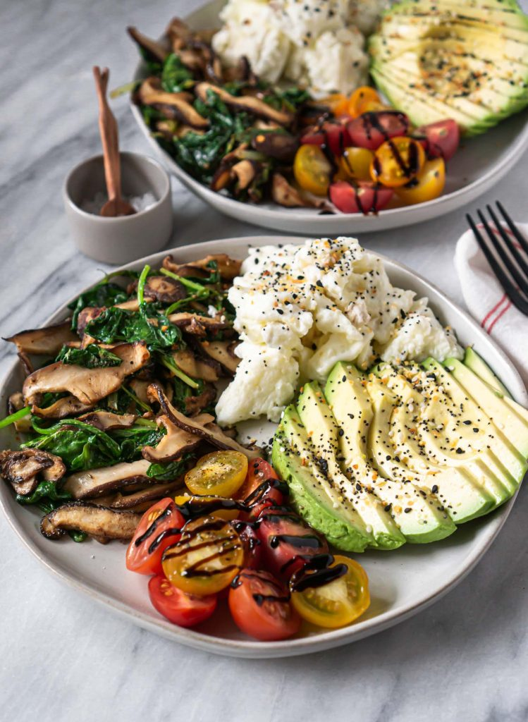 scrambled eggs, avocado, tomatoes, and mushrooms on a plate