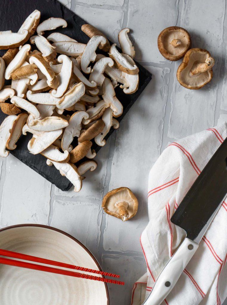 sliced shiitake mushrooms on a black slate board, red chopsticks, and a knife