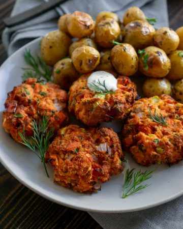 4 salmon cakes on a plate with roasted potatoes