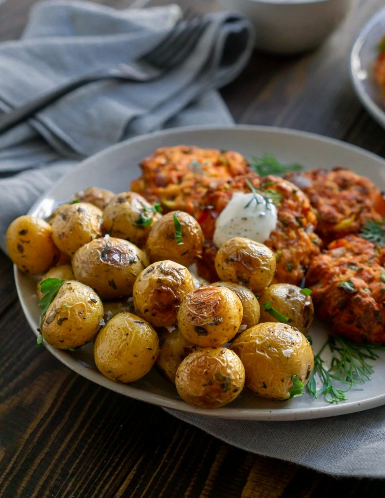 roasted mini potatoes on a plate with salmon cakes