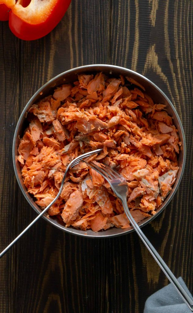 shredded salmon in a metal bowl with two forks